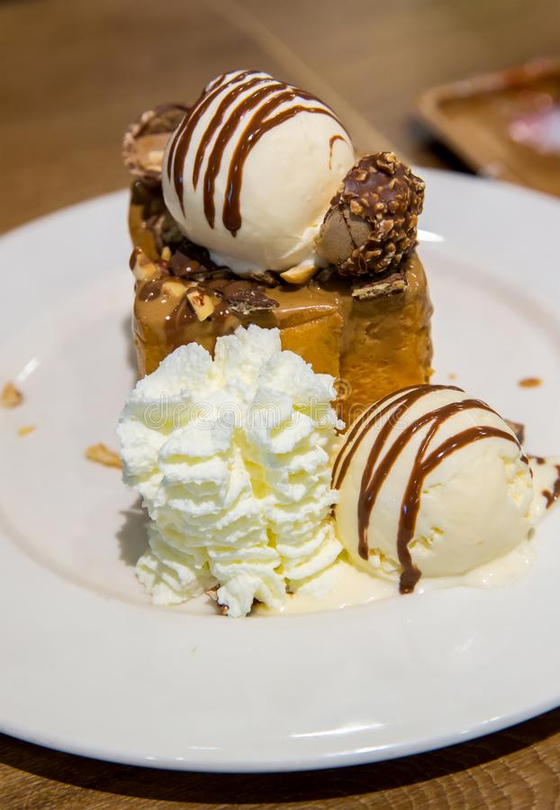Honey toast with vanilla ice cream and whiping cream topped with chocolate sauce on white dish. sweets bread and dessert. stock images