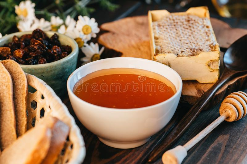 Honey in white ceramic bowl, honey dripper spoon, homemade honeycomb on rustic wooden table. Close up stock photos