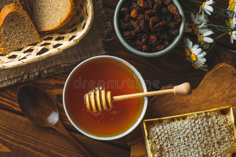 Honey in white ceramic bowl, honey dripper spoon, homemade honeycomb on rustic wooden table. Top view royalty free stock image