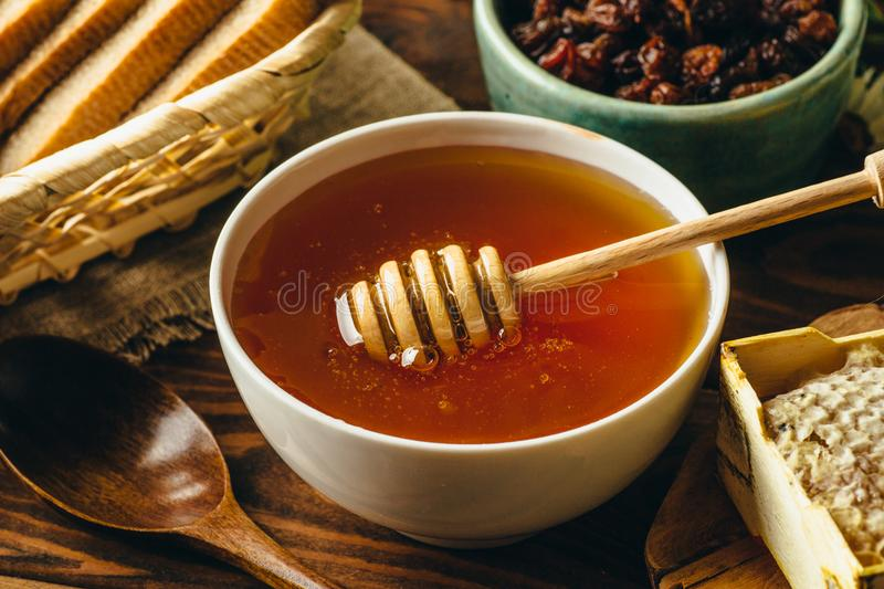 Honey in white ceramic bowl, honey dripper spoon, homemade honeycomb on rustic wooden table. Close up stock image