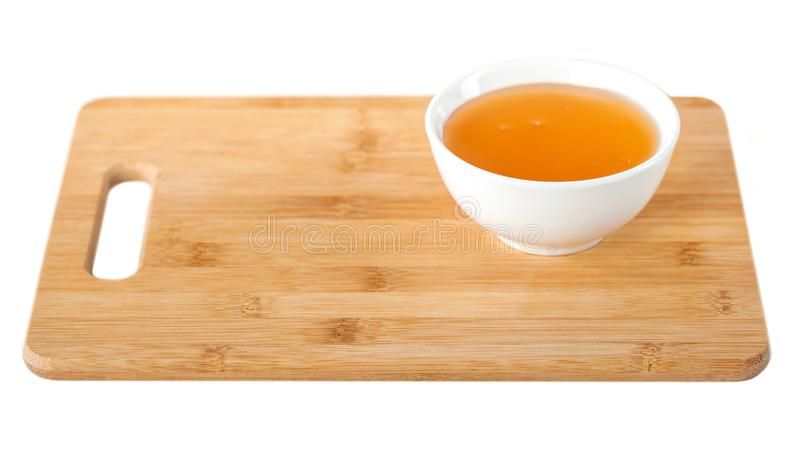 Honey in a white ceramic bowl on a wooden kitchen board, white background.  royalty free stock image