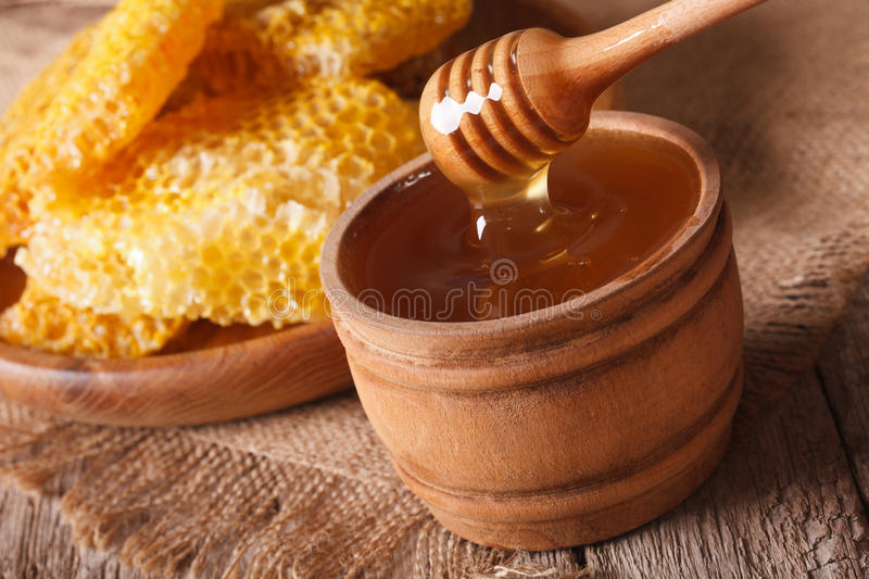 Honey in a wooden bowl and a honeycomb. horizontal, rustic. Honey in a wooden bowl and a honeycomb on the table. horizontal, rustic style stock photo
