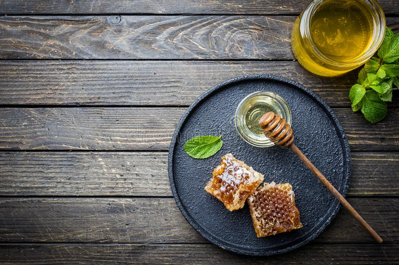 Honey with wooden honey dipper. And honeycomb on dark wood table, top view royalty free stock photo