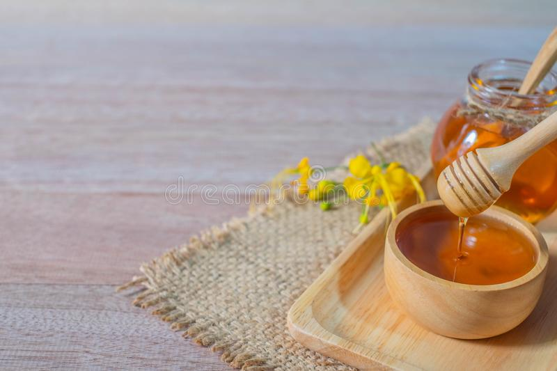 Honey in wooden honey dipper. On sack and wooden background royalty free stock photos