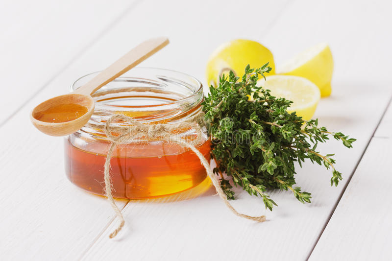 Honey in a wooden spoon and jar. On a white background stock photos