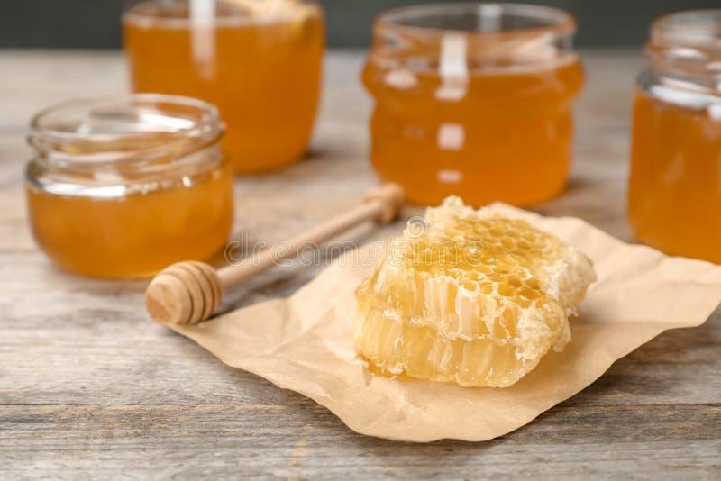 Honeycomb, chochla i słoje na stole, obraz stock
