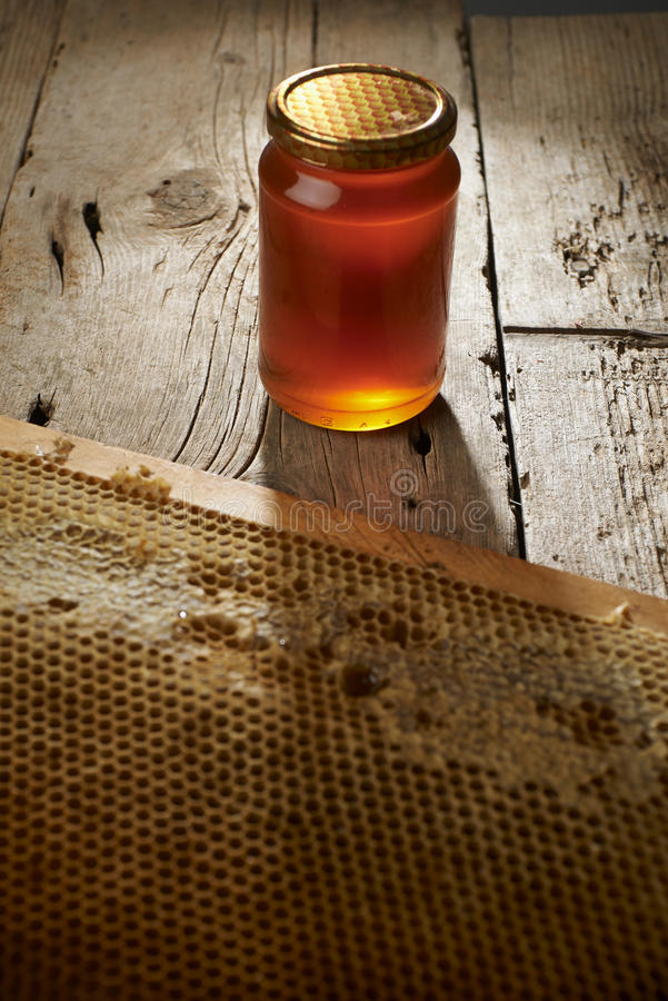 Honeycomb with fresh honey in a vase on wooden table. royalty free stock images