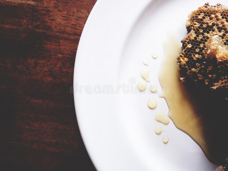 This is honeycomb and honey in white plate above the wooden, soft tone royalty free stock photo