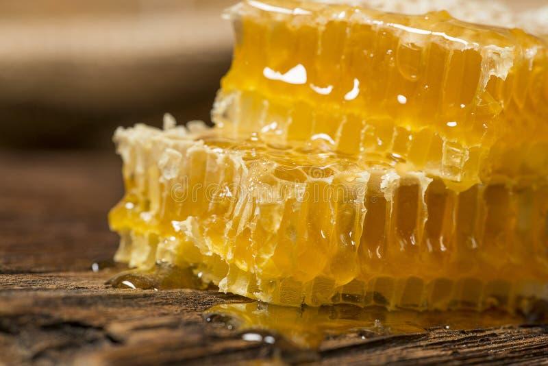 Honeycomb z miodem na drewnianym stole fotografia stock