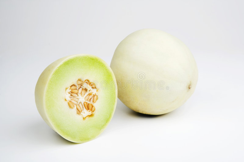 Honeydew Melon. Two halves of a honeydew melon on a white background royalty free stock image
