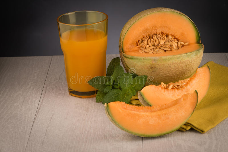 Honeydew melon juice. On a wooden table background royalty free stock photography