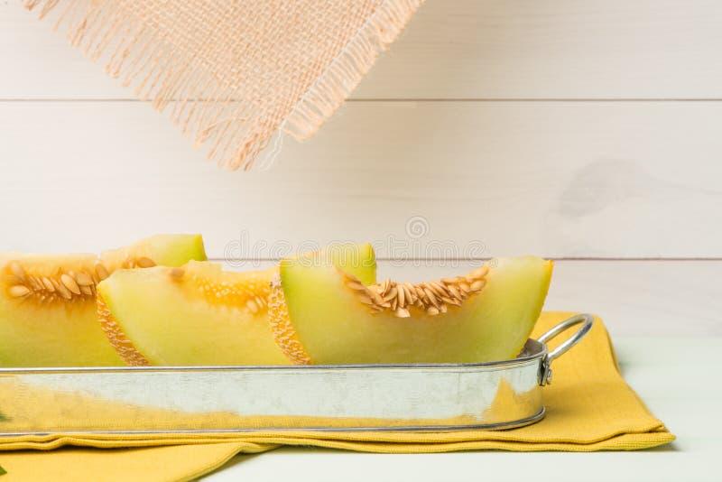 Honeydew melon. Juicy honeydew melon on a wooden table background stock photography