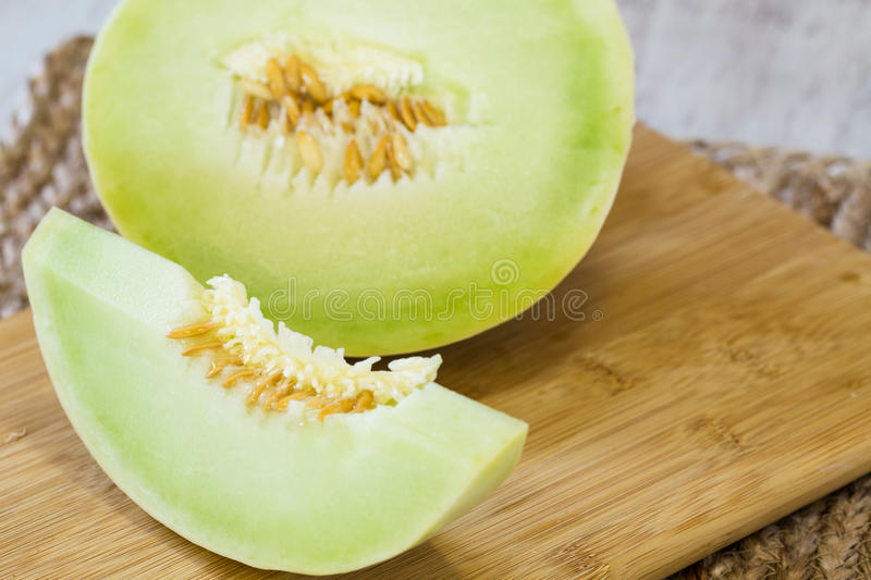 Honeydew Melon Slice on Wooden Cutting Board. Slice of honeydew melon close up on wooden cutting board for breakfast snack royalty free stock photography