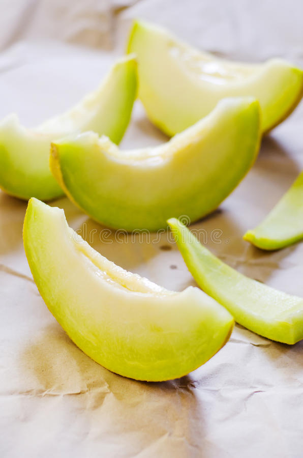 Honeydew melon. Slices on a rustic background stock photo
