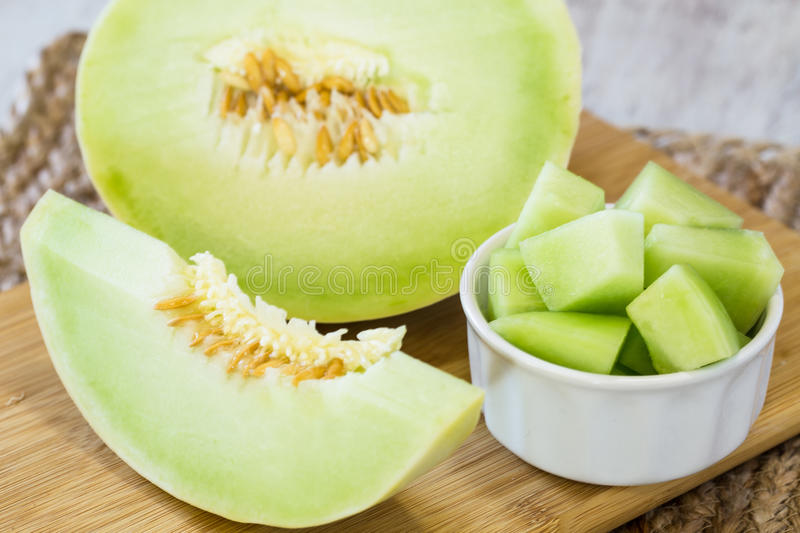 Honeydew Melon On Wooden Cutting Board For Breakfast Food. Honeydew melon slice and cut up pieces for breakfast snack diet food on cutting board royalty free stock photo