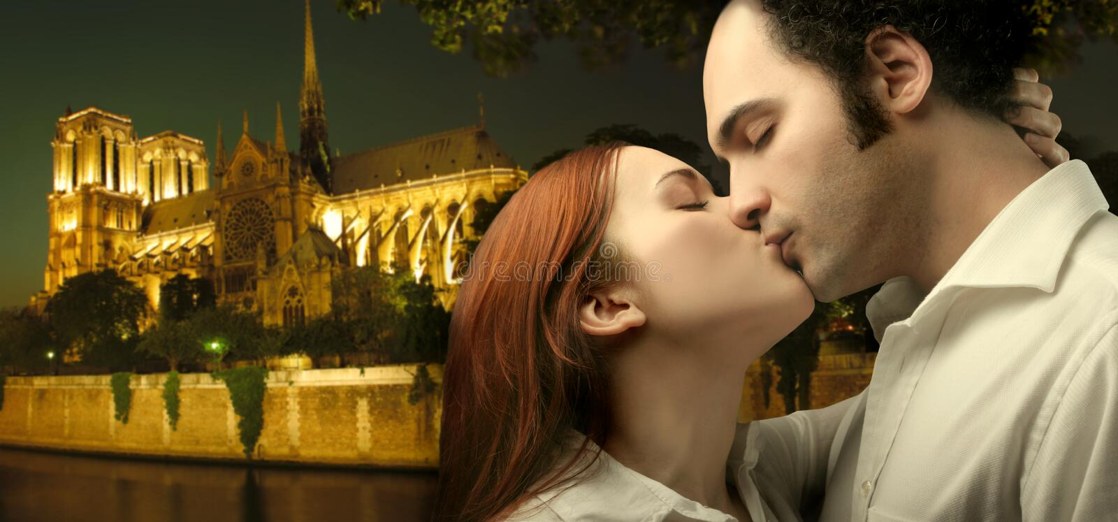 Honeymoon. Sweethearts kissing with notre dame on the background stock photography