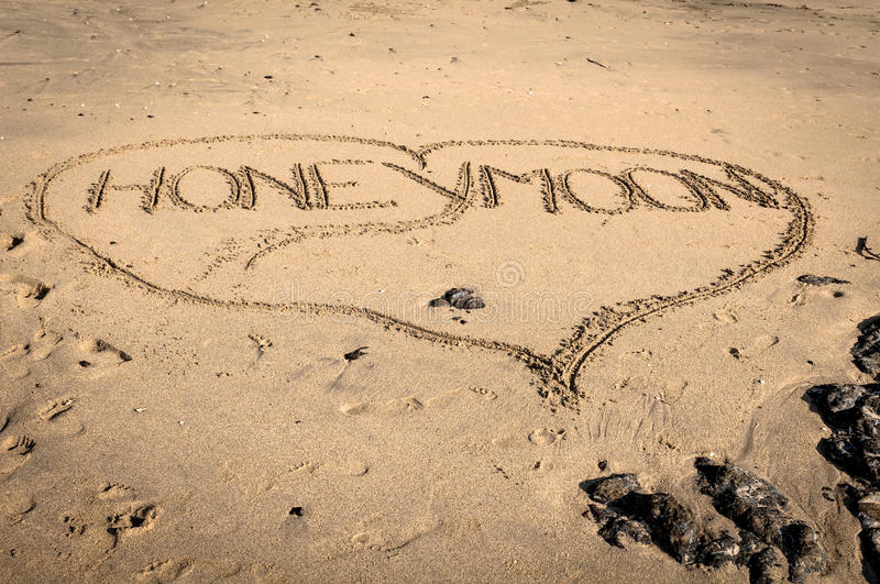 Honeymoon. Written on the sand in the outline of a heart royalty free stock photos