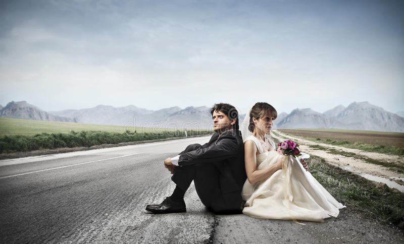 Honeymoon. Married couple sitting on the ground in a deserted road stock photos