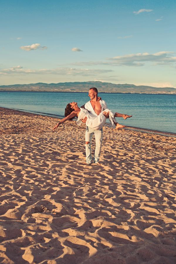 Honeymoon concept. honeymoon of young beautiful couple with man holding woman on hands on sandy beach. stock image