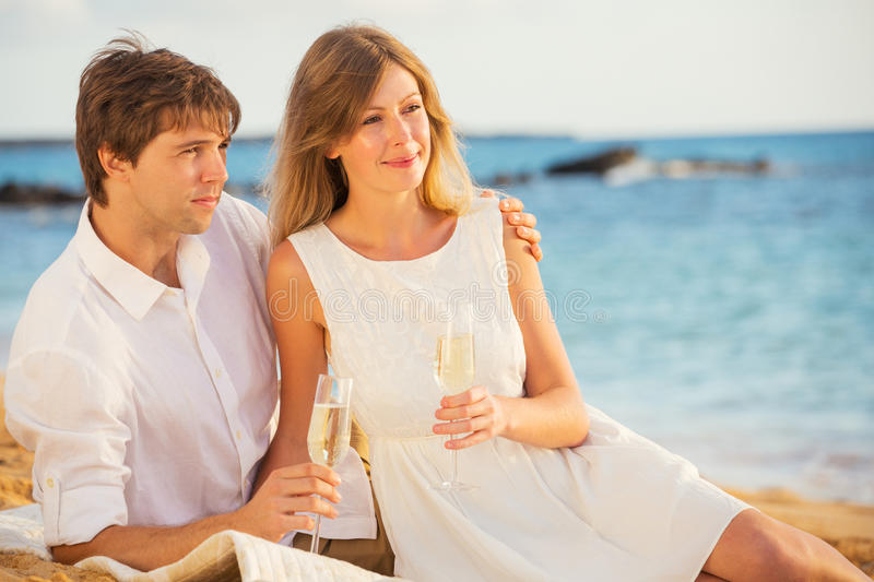 Honeymoon concept, Man and Woman in love. Man and Woman in love, Couple enjoying glass of champagne on tropical beach at sunset, Honeymoon concept royalty free stock image