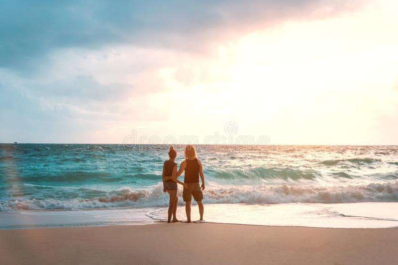 Honeymoon couple in love embracing and enjoying ocean view at beach stock photography