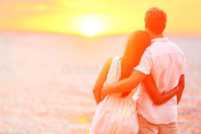 Honeymoon couple romantic in love at beach sunset. Newlywed happy young couple embracing enjoying ocean sunset during travel holidays vacation getaway royalty free stock images