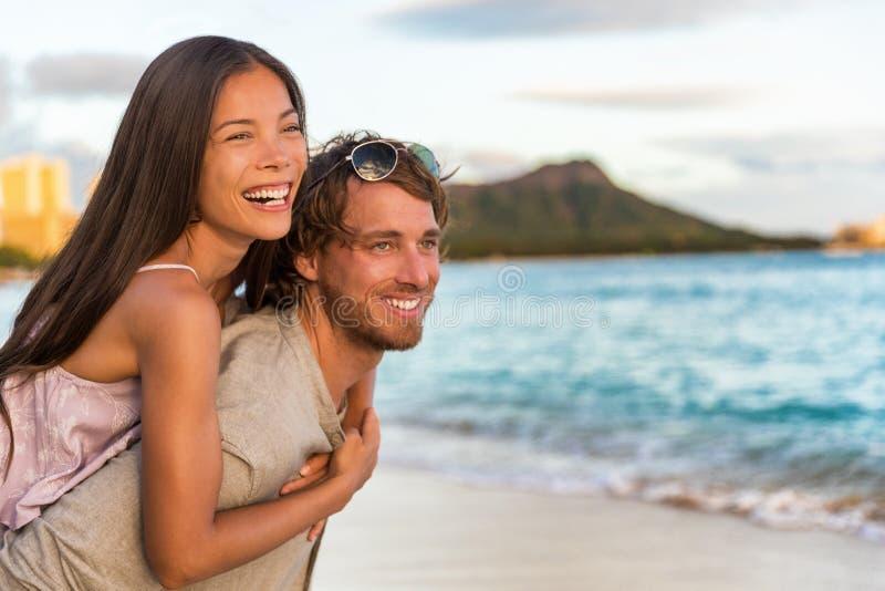 Honeymoon Hawaii strandvakantieparen piggyback Multiraciale mensen die verliefd zijn op reisvakantie, Waikiki-strand, Honolulu, H royalty-vrije stock foto's