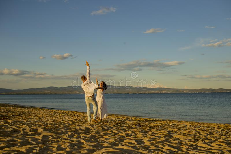 Honeymoon, just married concept. Man and woman dancing, couple happy on vacation. Couple in love running on beach stock photography