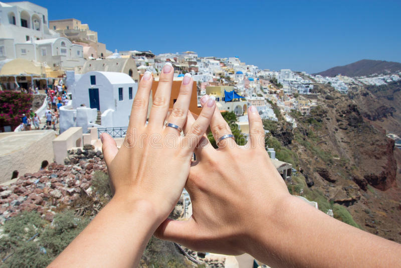 Honeymoon on Santorini island - hands with wedding rings over pa royalty free stock photography