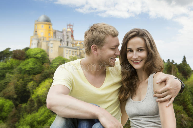 Honeymoon Travel to Europe. Young couple in love hugging on the background of Pena Palace in Sintra Portugal royalty free stock image