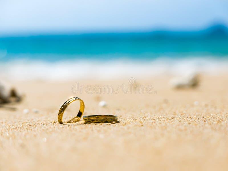 honeymoon Twee trouwringen op zandig strand stock foto
