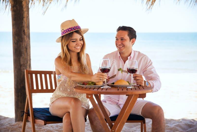 Honeymooners имея полезного время работы на пляже стоковое изображение rf