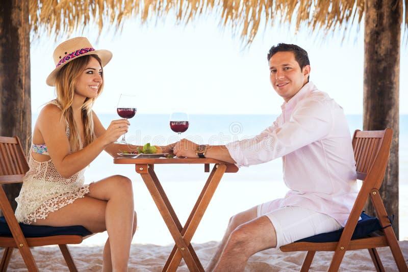 Honeymooners che bevono vino alla spiaggia immagini stock
