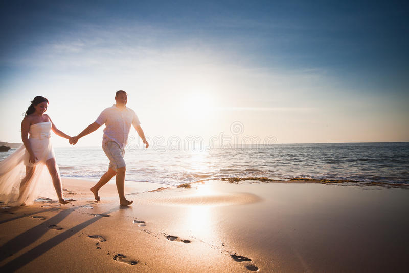 Honeymooners couple just married running at beach. Honeymooners happy couple dressed in white running or jogging on the beach stock photo