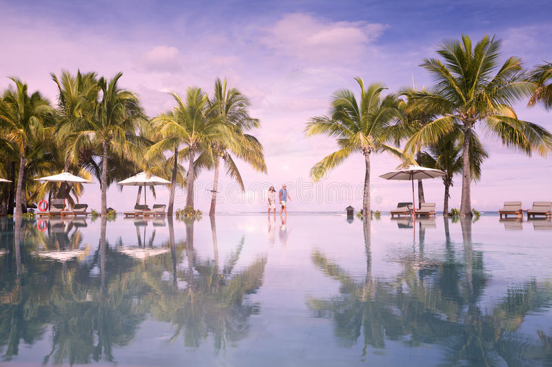 Honeymooners o tropical island of Mauritius, sunbeds with palm leaf thatch roofing umbrellas. Honeymoon 5 star resort on Mauritius royalty free stock images