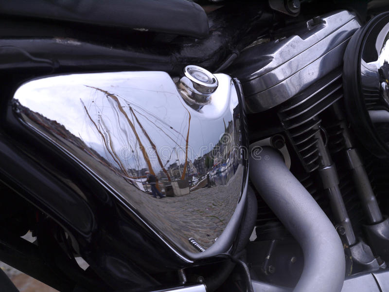 Honfleur refected in the oil tank of a Harley-Davidson motorcycle. Engine and exhaust to view stock photo
