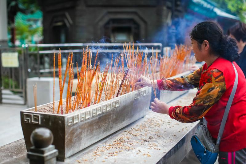 HONG KONG APRIL 2018 - chinese lady is praying in Wong Tai Sin temple. woman lights incense in the temple royalty free stock photos