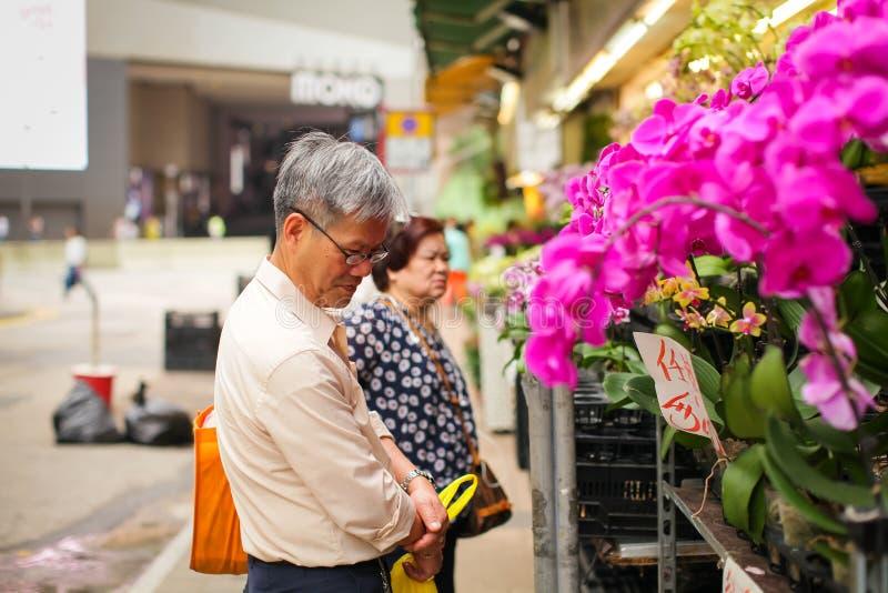HONG KONG - APRIL 2018: de bejaarde Aziatische mens kiest diverse beautyful roze orchidee in potten in de markt van de straatbloe royalty-vrije stock fotografie