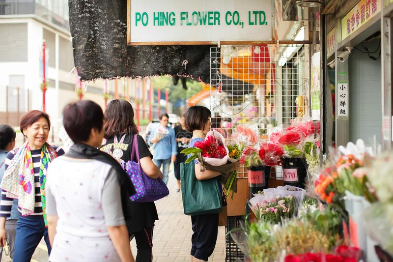 Hong Kong - April , 2018: flower market in Kowloon, Hong Kong, Asian Woman picks flowers for party or celebration. royalty free stock image