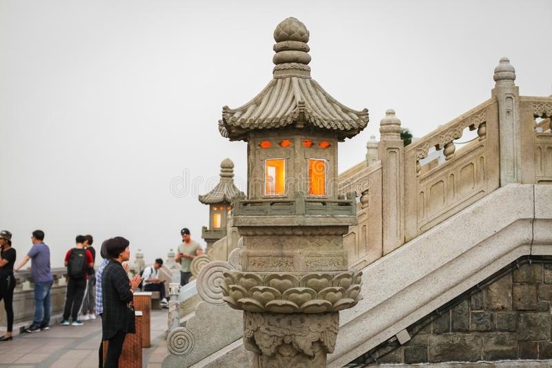 HONG KONG _ APRIL 2018 stone Chinese Buddhist lamp with light inside near big buddha in Hong Kong. royalty free stock photography