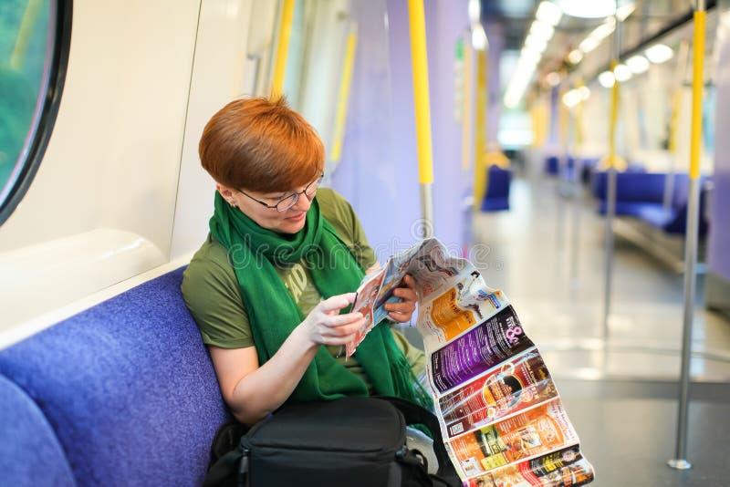 HONG KONG april 2018 - Vrouwenzitting aan de gang en bestuderend routekaart Kaukasische toerist in wagen van metro reiziger in de stock afbeeldingen