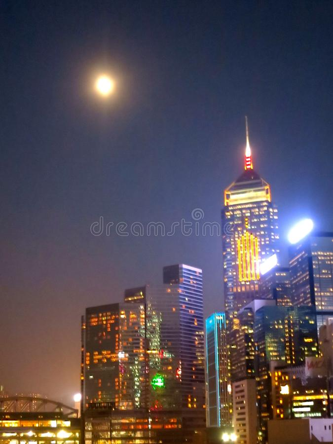 Hong Kong Buildings at Night, with Bright Lights. HONG KONG - NOV. 2013 - Buildings in Admirlty district are lit up bright with lights at night, and the moon is stock photo