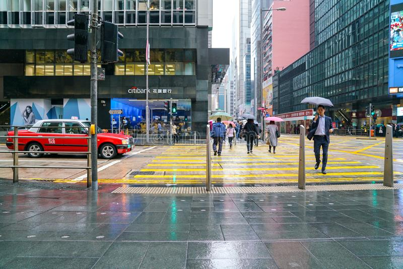Hong Kong Central. People walking on the street. Rainy day. Central, Hong Kong-14th March 2019: People walking and crossing the street on a rainy day royalty free stock photo