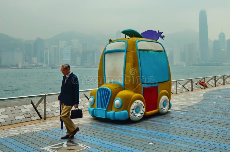 HONG KONG, CHINA - 29 DE ABRIL DE 2014: Um homem chinês idoso anda ao longo da avenida das estrelas Tempo enevoado, triste na ter fotografia de stock royalty free