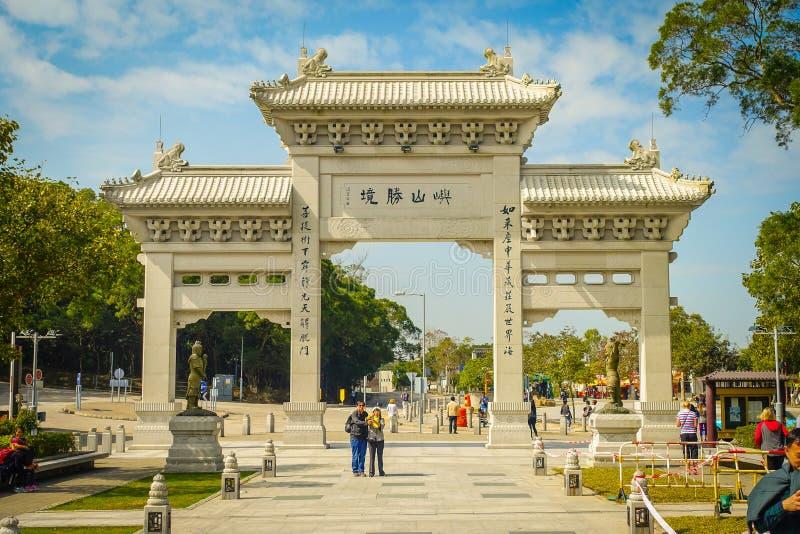HONG KONG, CHINA - 26 DE ENERO DE 2017: Gente no identificada que camina en la puerta de la entrada al monasterio de Tian Tin y a imagen de archivo libre de regalías