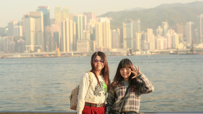 Hong Kong, China - January 1, 2016: Two young chinese tourist girls posing positively on the coast in Hong Kong, against stock image
