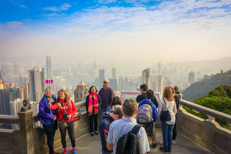 HONG KONG, CHINA - JANUARY 22, 2017: Unidentified people taking pictures from Victoria Peak to the city of Hong Kong in royalty free stock photos