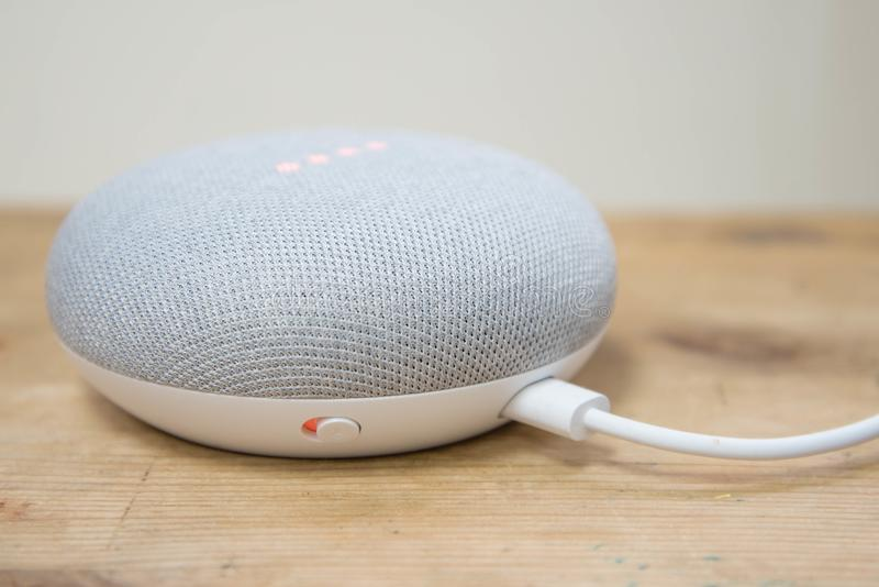 Hong Kong, China - 11 March, 2018: Physical microphone switch button of the Google Home Mini Chalk color on a wooden surface stock image