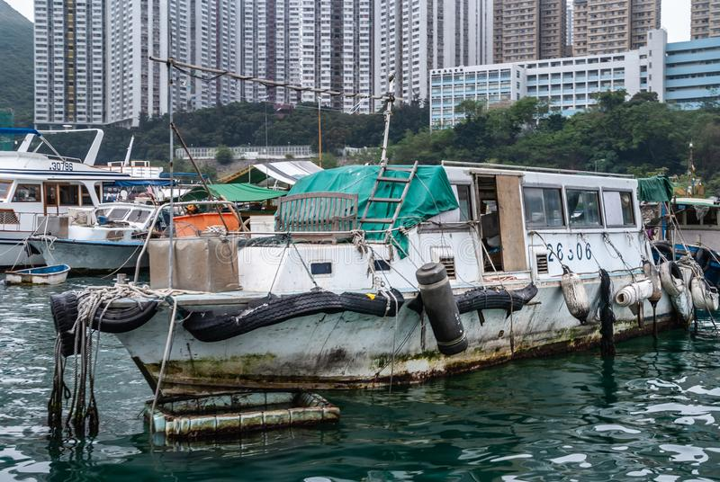 Closeup of delapidated Houseboat in harbor of Hong Kong, China. Hong Kong, China - May 12, 2010: Closeup of dilapidated white houseboat in harbor. Other vessels royalty free stock photo