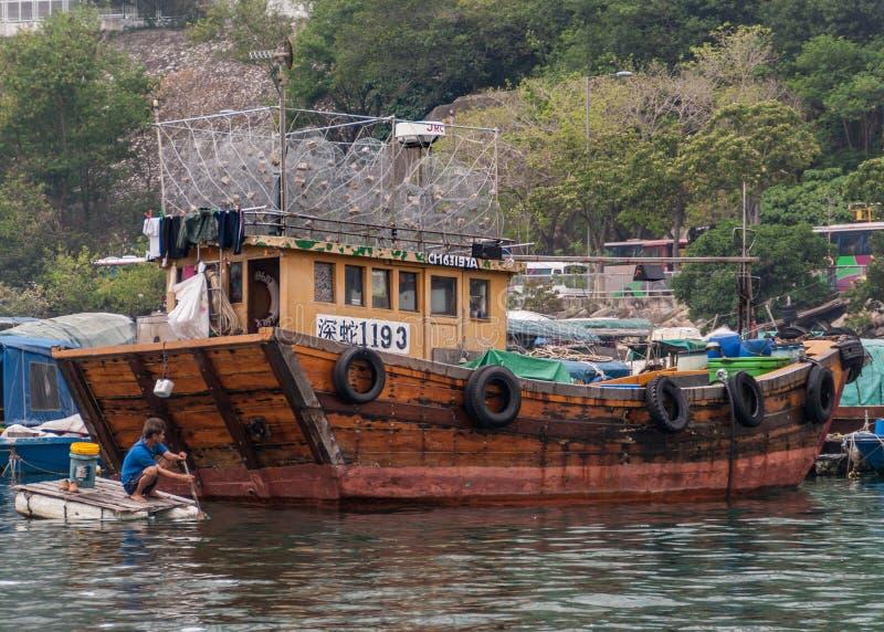 Closeup of fishing sampan in harbor of Hong Kong, China. Hong Kong, China - May 12, 2010: Closeup of fishing wooden brown sampan in harbor. Other vessels moored royalty free stock images